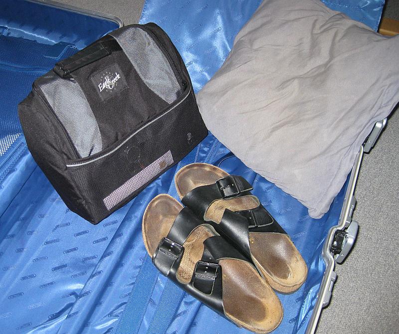Drei Dinge, die auf Reisen bei mir nie fehlen: Kissen, Schlappen und Kulturbeutel